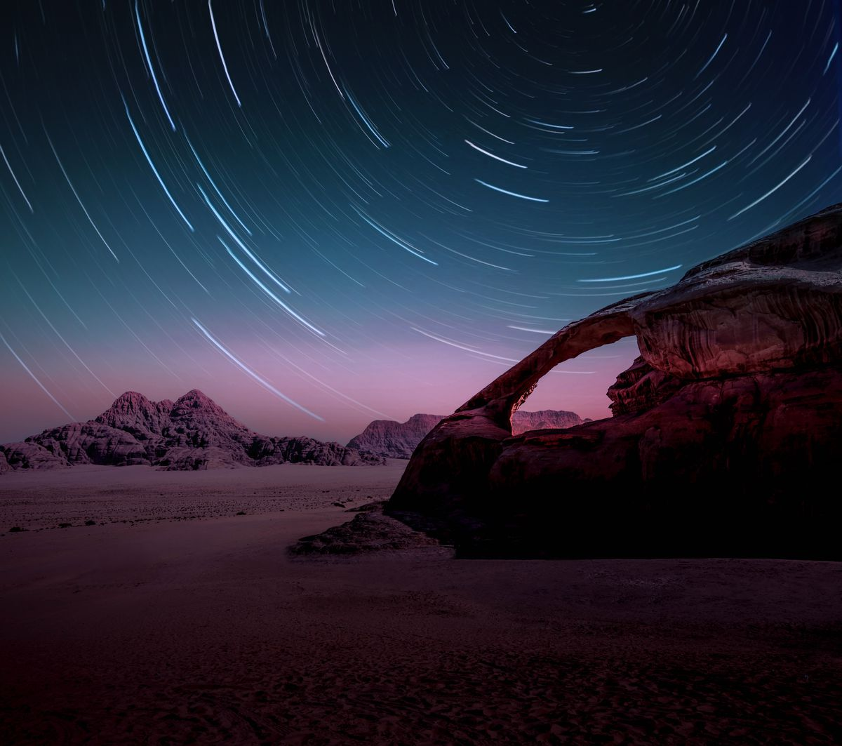 A long exposure of the stars in the Wadi Rum desert of Jordan with natural arch.