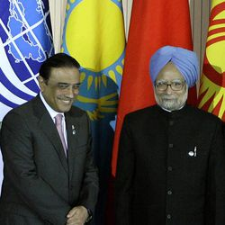 FILE - In this June 16, 2009 file photo, Pakistan's President Asif Ali Zardari, left, and Indian Prime Minister Manmohan Singh pose for a photo during a summit of the Shanghai Cooperation Organization in the Ural Mountains city of Yekaterinburg, Russia. Zardari's trip to India on Sunday, April 8, 2012, is a milestone in the warming relations between the neighbors. But, officially, he is just sharing a quick lunch with the India's leader on his way to visit a Muslim shrine.