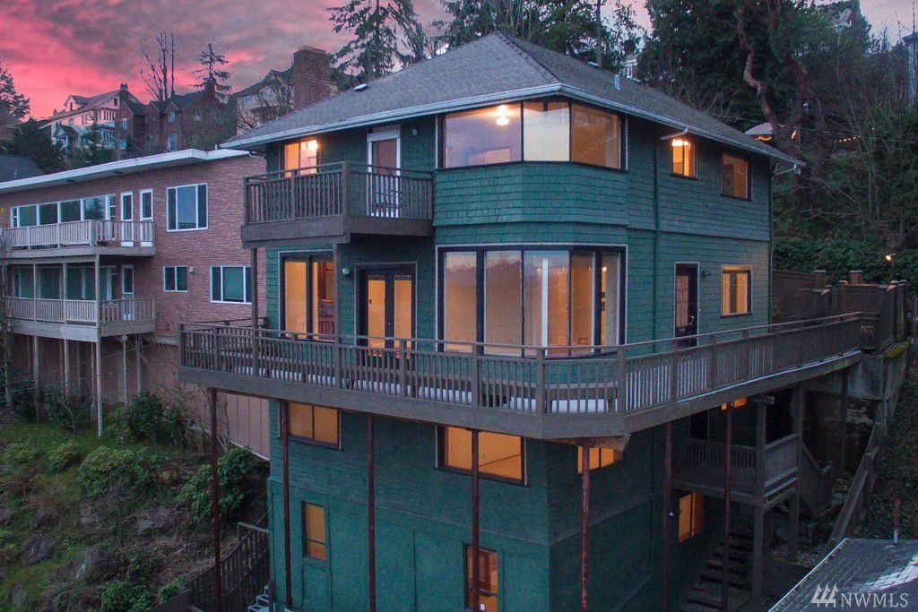 A four story green house with a wraparound deck halfway down