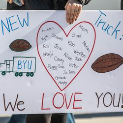 Friends, family, and neighbors hold signs as they gather to watch Brandon Stewart go for a ride in BYU football's equipment semi in Clinton on Saturday, Jan. 30, 2021. The ride was his final wish as he battles cancer.
