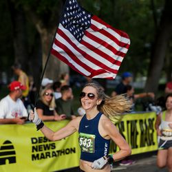 Kim Kapinos carries an American flag as she finishes the Deseret News Half Marathon at Liberty Park in Salt Lake City on Friday, July 23, 2021.