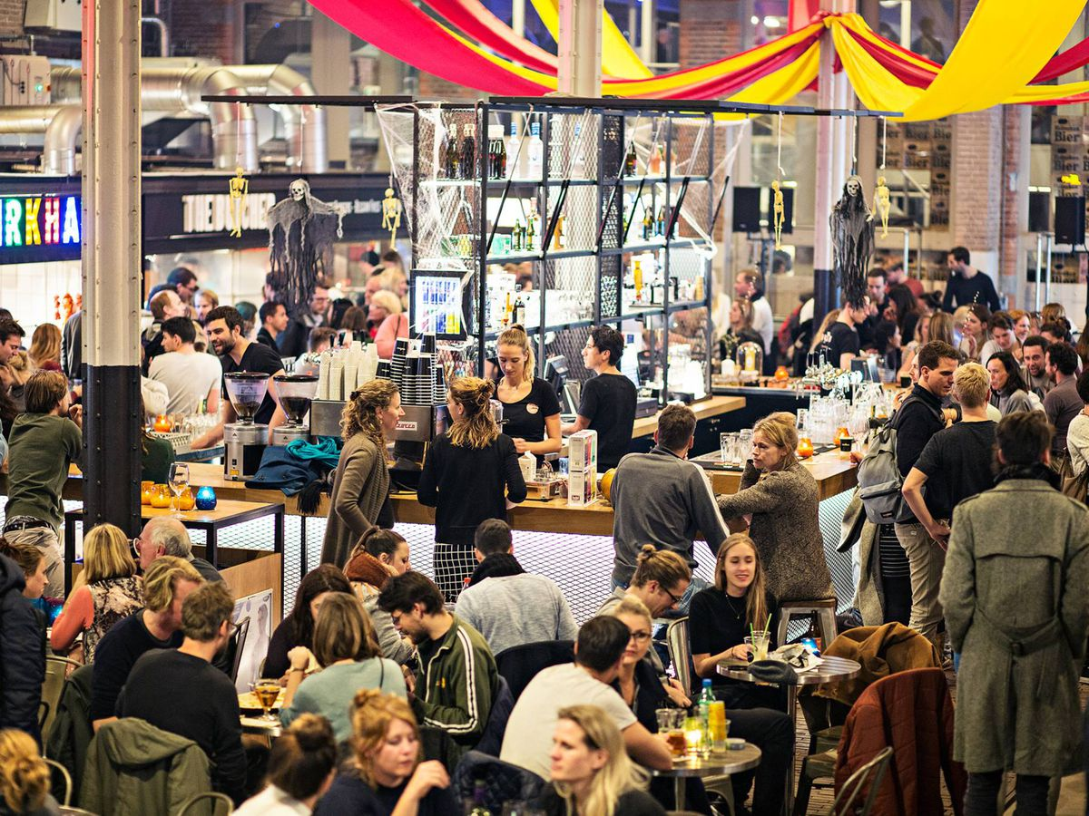 A crowd gathers at various stands in the Foodhallen food hall, a large space with high ceilings, streamers hanging from above, and semi-industrial materials.