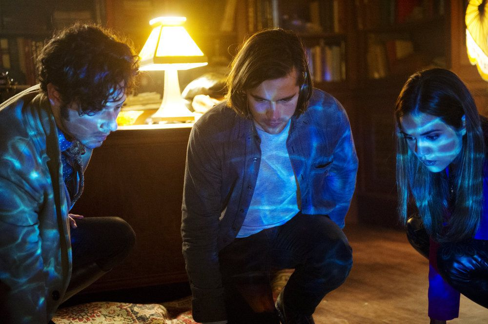 """Three actors in """"The Magicians"""" kneel on the floor and look at a glowing blue light."""