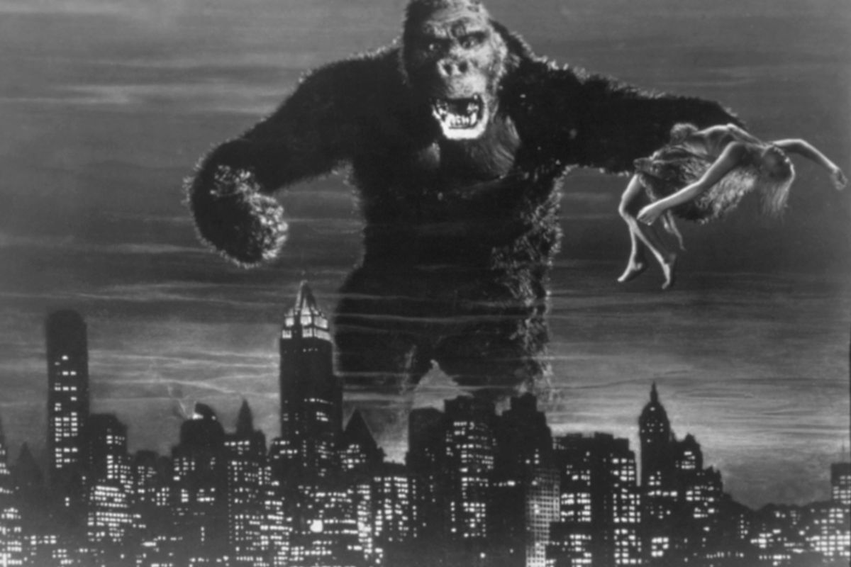 """A movie still from """"King Kong"""" showing the ape holding a woman and rampaging across a city skyline"""