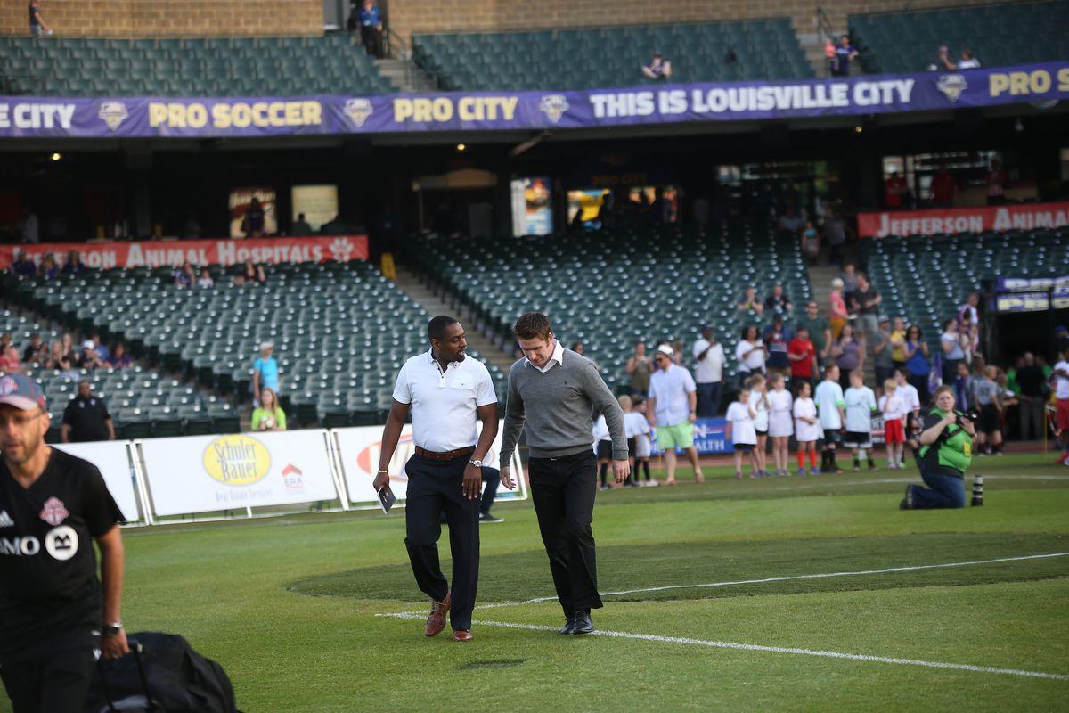 USL photo coaches Bent & O'Connor walk towards their benches