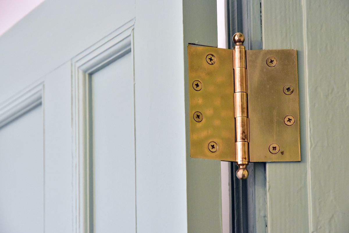 A close up of a door hinge mounted on a mossy green door and frame.