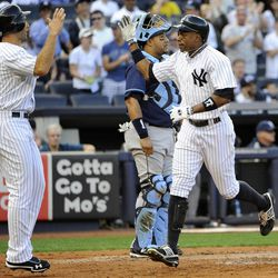 New York Yankees' Curtis Granderson, right, runs past Tampa Bay Rays catcher Jose Molina to high-five Raul Ibanez (27) after hitting a two-run home run off of Rays' James Shields that scored Ibanez in the second inning of a baseball game, Saturday, Sept. 15, 2012, at Yankee Stadium in New York.