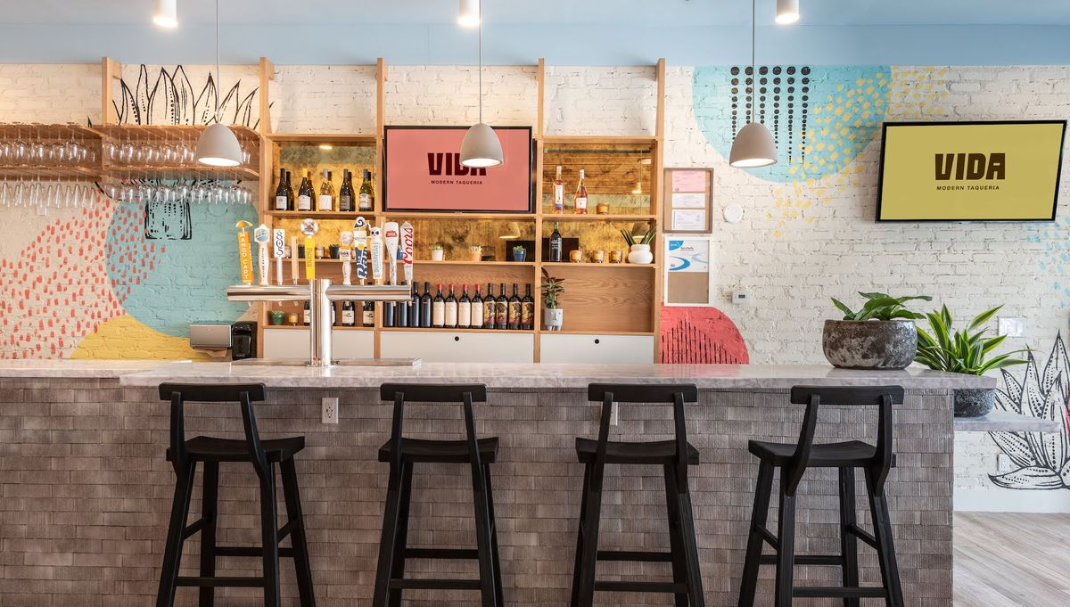 A straight-on look at a small interior bar with a white painted brick background at a modern taqueria restaurant.