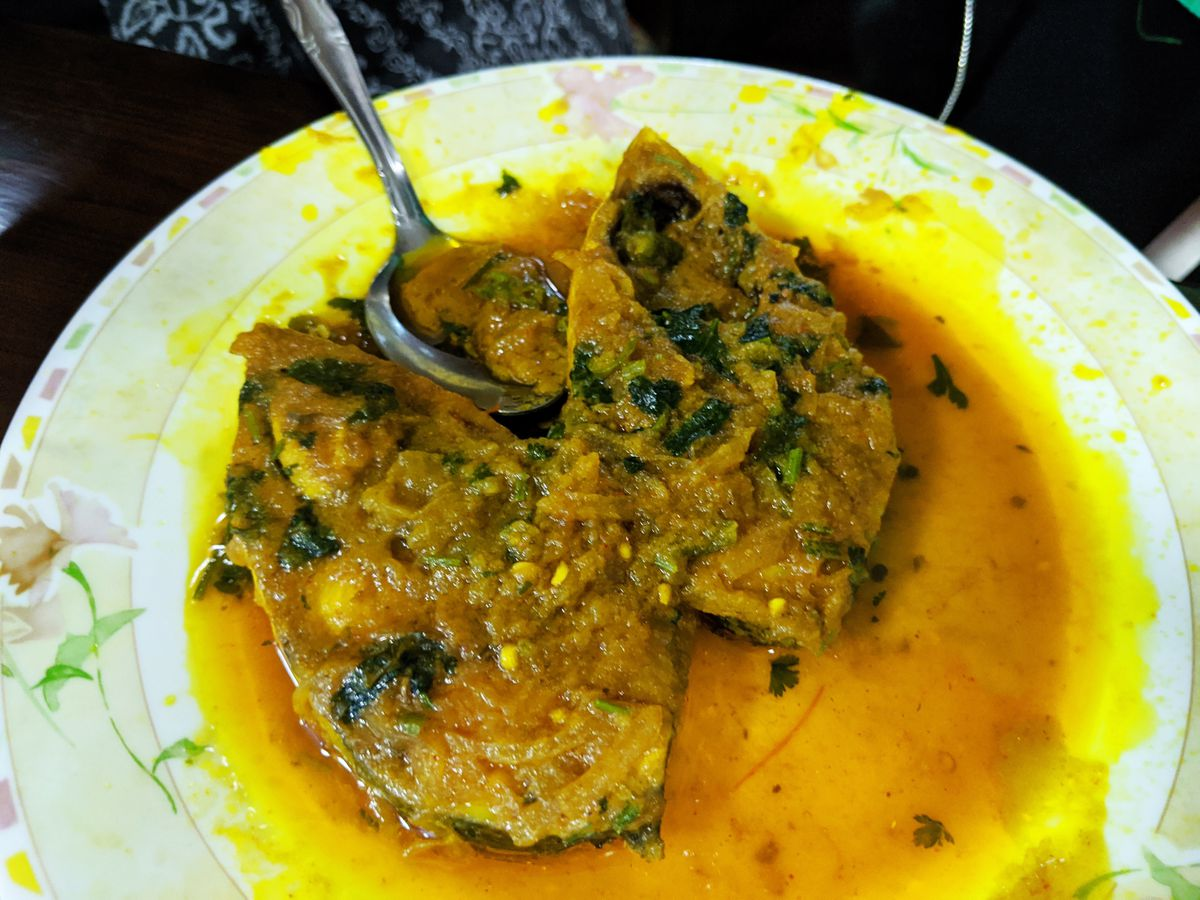 Two fish filets covered in a chunky and oily yellow sauce.