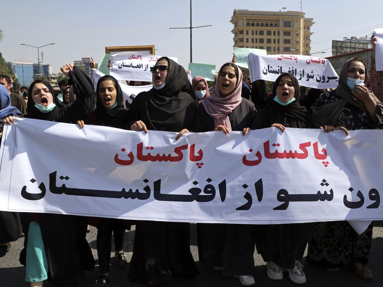 """Afghans shout slogans during an anti-Pakistan demonstration, near the Pakistan embassy in Kabul, Afghanistan, Tuesday, Sept. 7, 2021. Sign in Persian reads, """"Pakistan Pakistan Get out of Afghanistan."""""""