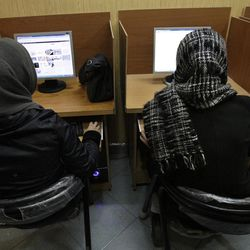 FILE- In this Monday, Feb. 13, 2012 file photo, Iranian women use computers at an Internet cafe in central Tehran. Iran's cyber monitors often tout their efforts to fight the West's 'soft war' of influence through the web, but trying to ban Google's popular Gmail may have gone too far with complaints coming even from email-starved parliament members.