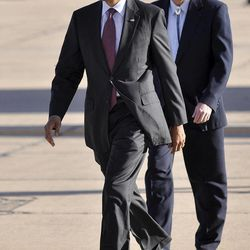 President Barack Obama, left, and Secretary of the Interior Ken Salazar, right, walk to meet supporters after exiting Air Force One at the Roswell International Air Center in Roswell, N.M., Wednesday, March 21, 2012.