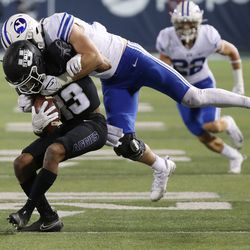 Brigham Young Cougars linebacker Max Tooley (31) tackles Utah State Aggies wide receiver Deven Thompkins (13) in Logan on Friday, Oct. 1, 2021.