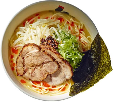 A bowl of ramen with meat, seaweed, and greens