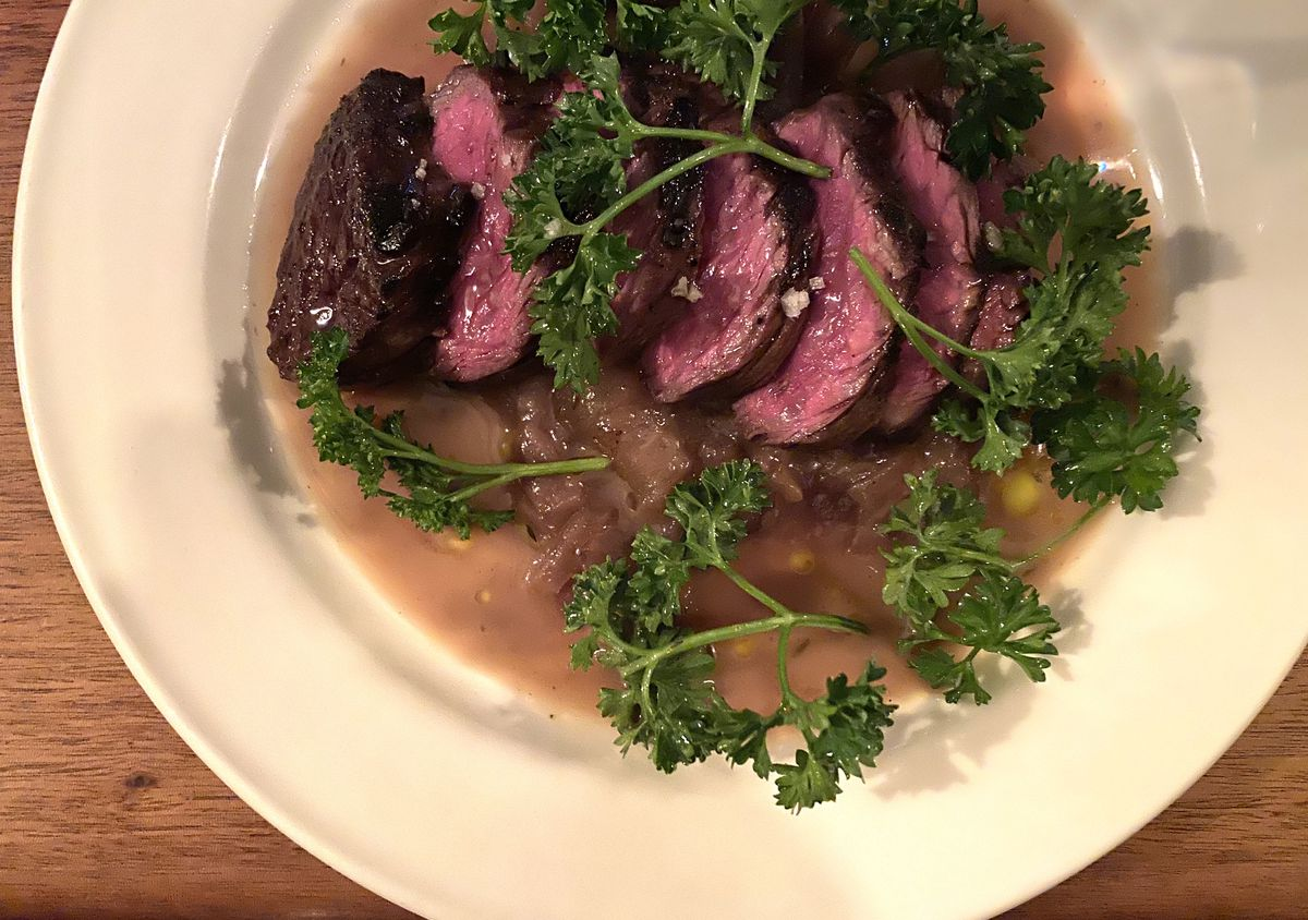 Medium-rare hanger steak sits over a bed of onions at Anton's