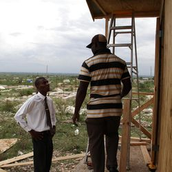 Berthony Theodor checks on construction of one of 200 homes the LDS Church is building for members who lost homes in the January 2010 earthquake. Here, a local LDS Bishop is supervising the construction.