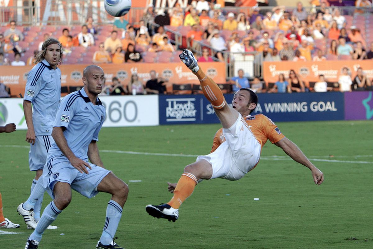 HOUSTON - JULY 16:  Brad Davis #11 of the Houston Dynamo puts a shot back on goal in front of Aurelien Collin #78 and Chance Myers #7 at Robertson Stadium on July 16, 2011 in Houston, Texas.  (Photo by Bob Levey/Getty Images)