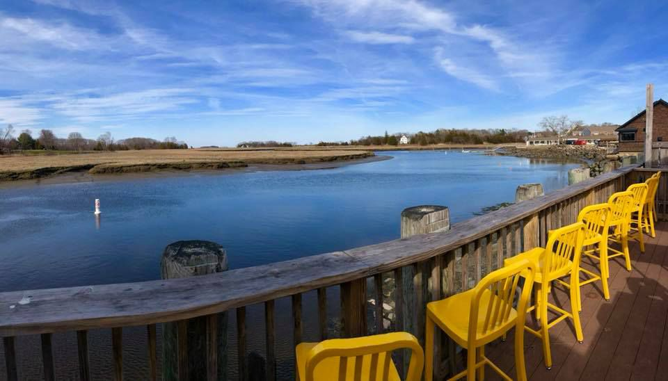 Marshland waterfront view from a wooden deck lined with yellow chairs