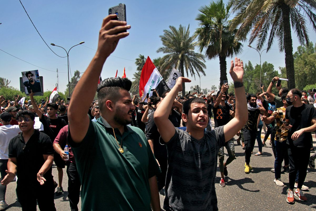 Anti-government protesters chant slogans as they hold posters of slain activists outside the Green Zone area which houses the seat of the country's government and foreign embassies, in Baghdad, Iraq, Tuesday, May 25, 2021. Hundreds of Iraqi protesters have taken to the streets of Baghdad to decry a recent spike in assassinations targeting outspoken activists and journalists.