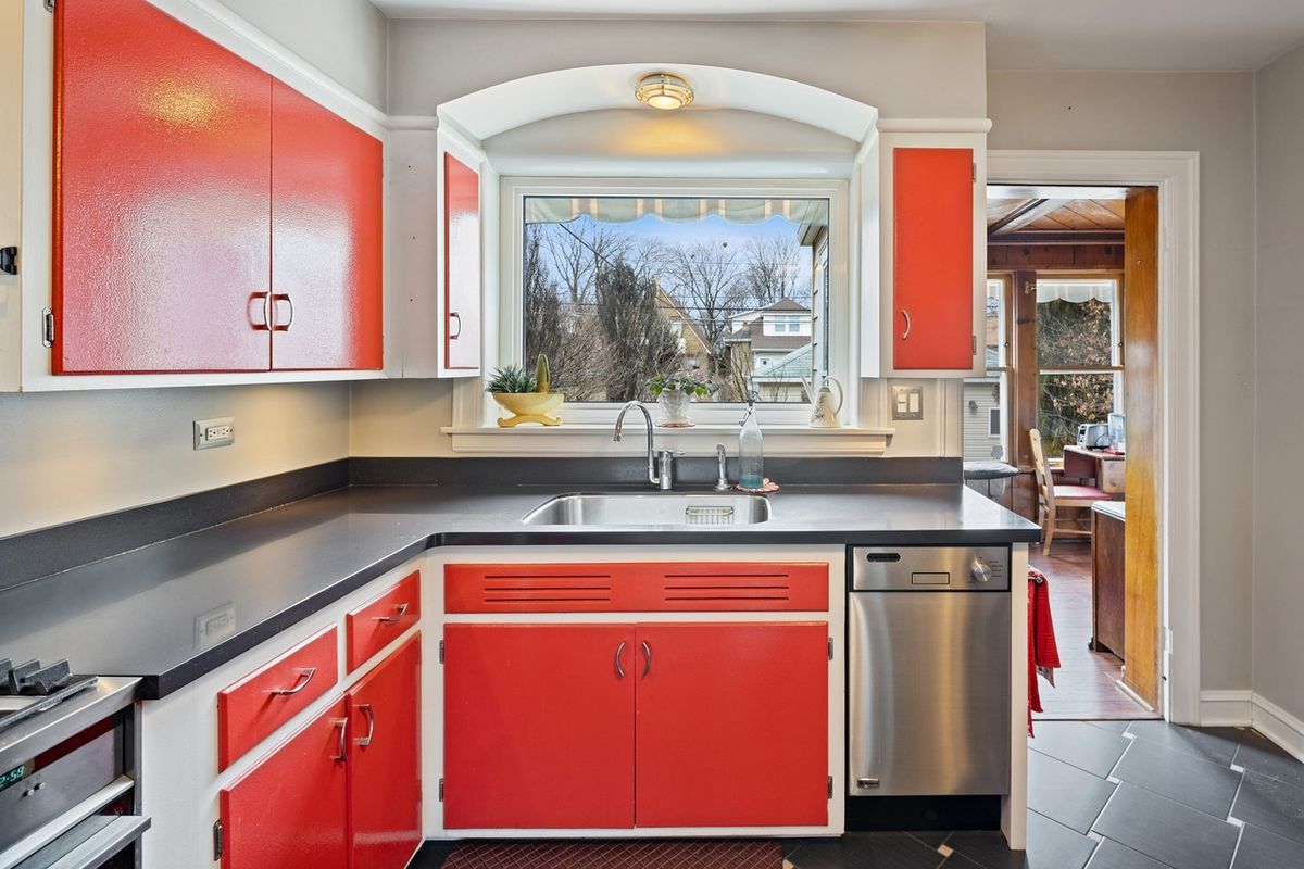 A small kitchen with red cabinets, a large window over the sink, and black tile with black countertops.