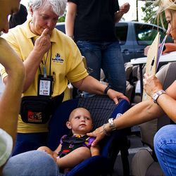 Jeremy Nef, Taylorsville, left, Carol Avery and Annette Gomez decide whether a car seat is a good fit for Ginger Nef.