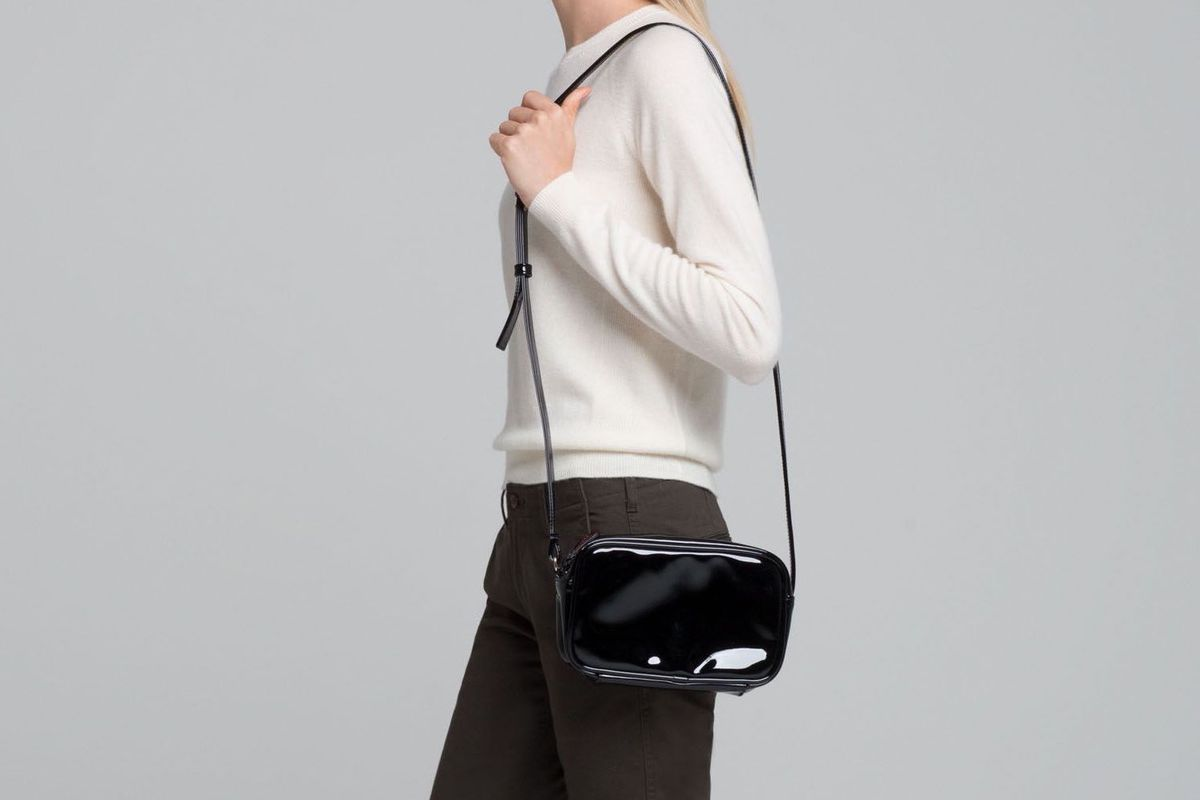 A woman holding a black patent leather bag