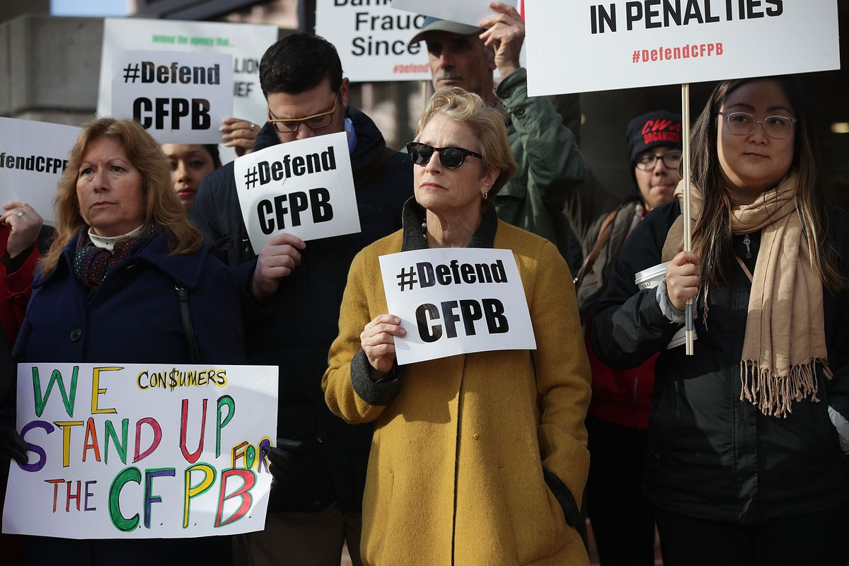 Supporters of the Consumer Financial Protection Bureau hold signs as they gather in front of the agency November 27, 2017 in Washington, DC.