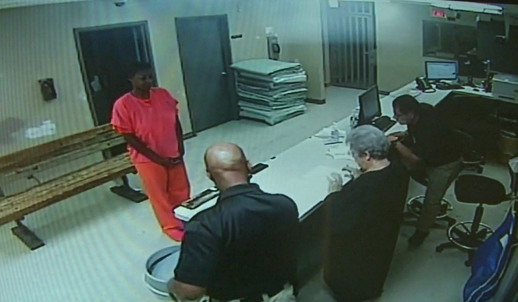 In an image from a video provided by the Waller County, Texas, Sheriff's Department, Sandra Bland stands in front of a desk at the Waller County Jail in Hempstead, Texas. Waller County Sheriff's Department via AP