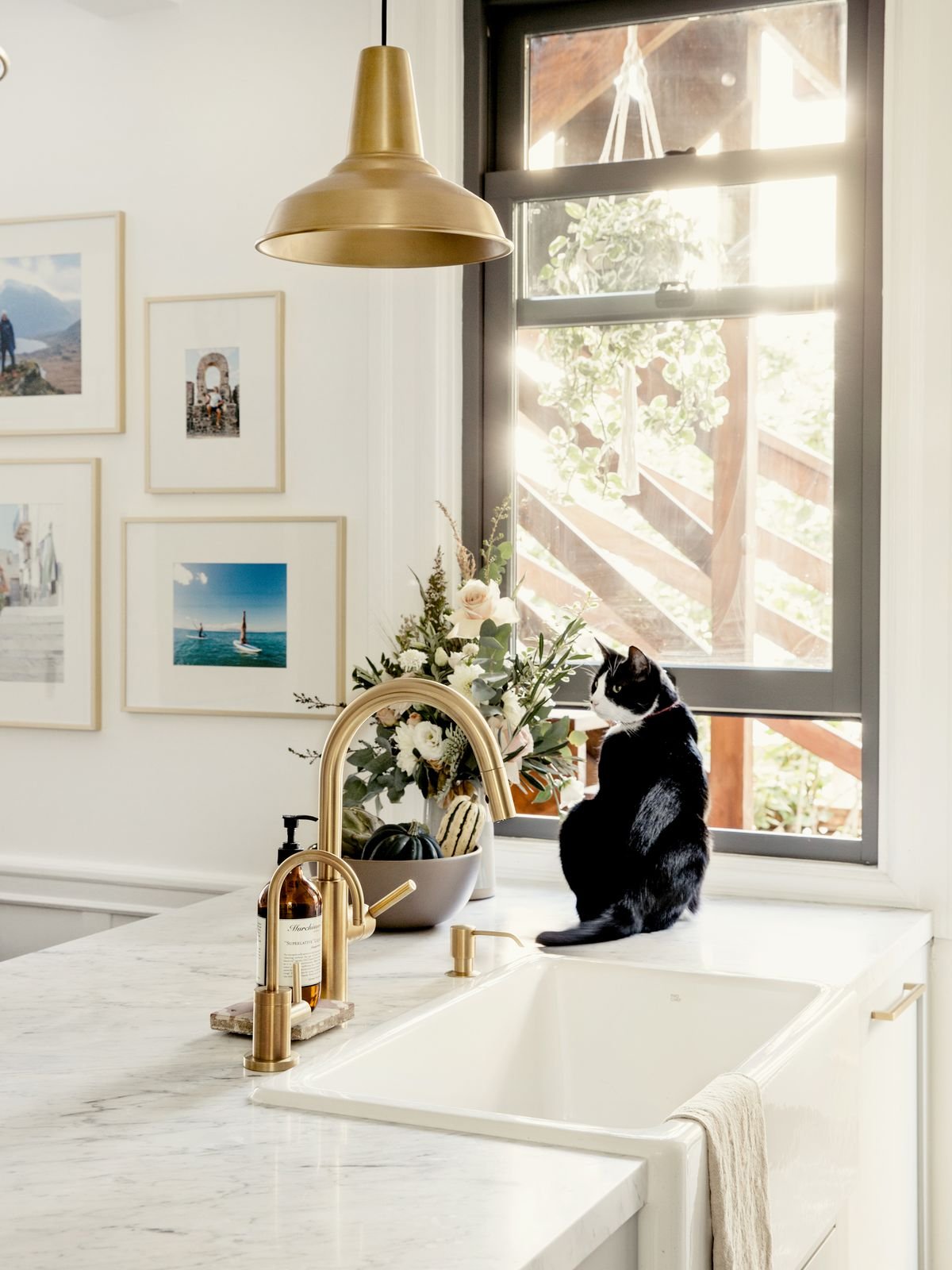 A kitchen island with a marble top and brass sink fixtures. A black and white cat sits next to the sink. There is a window letting in light. There are multiple works of art hanging on the wall.