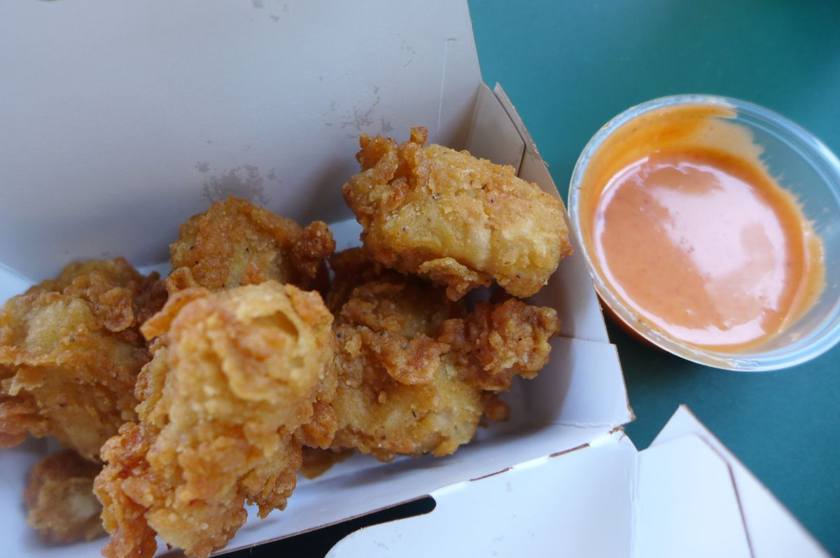 A box of chicken nuggets with a plastic cup or orange sauce on the side.