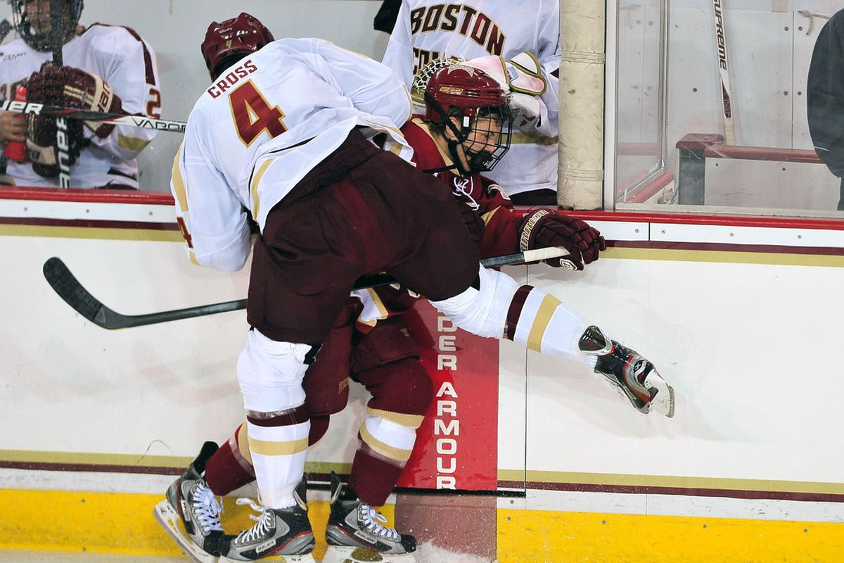 October 14, 2011; Boston MA, USA; Boston College Eagles defenseman Tommy Cross (4) hits Denver Pioneers winger Luke Salazar (18) in the first period at Conte Forum. Mandatory Credit: Andrew B. Fielding-US PRESSWIRE