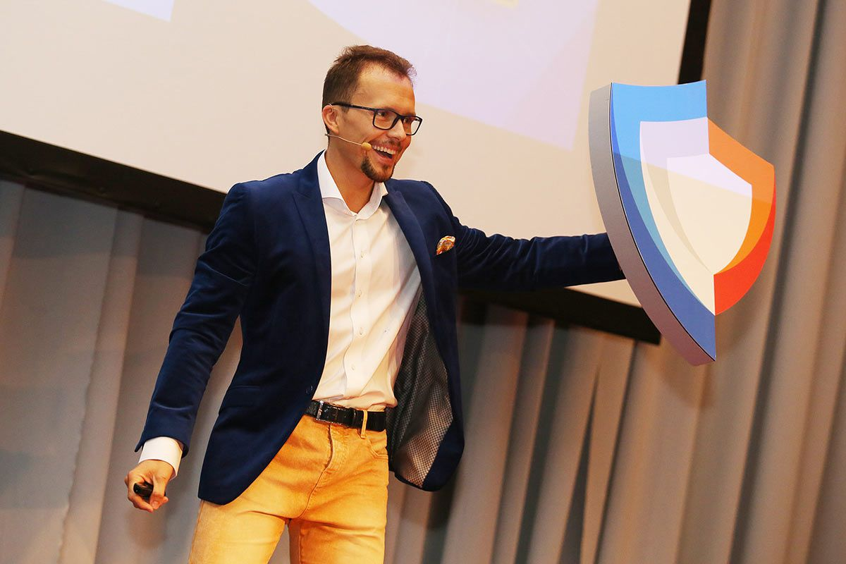 a man in a blue blazer and yellow pants holds up a shield logo