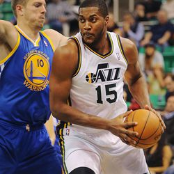 Utah's Derrick Favors works around Warriors' David Lee as the Utah Jazz and the Golden State Warriors play Tuesday, Oct. 8, 2013 in preseason action at Energy Solutions arena in Salt Lake City.