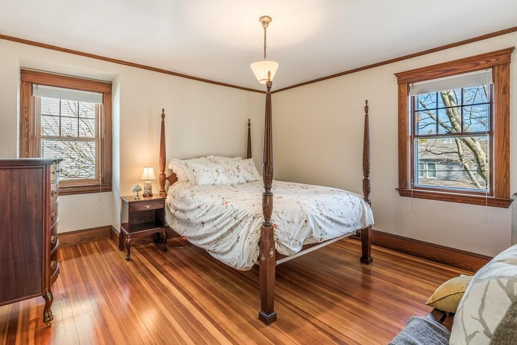 A bedroom with a four-post bed and two windows facing it each other near a corner.