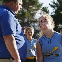 Brad Thomas, left, who has been coaching his daughter's accelerated softball team for the past five years, calms his daughter, Faith Thomas, down during a scrimmage at Dewey Bluth Park in Sandy, Utah, Thursday, June 9, 2016.