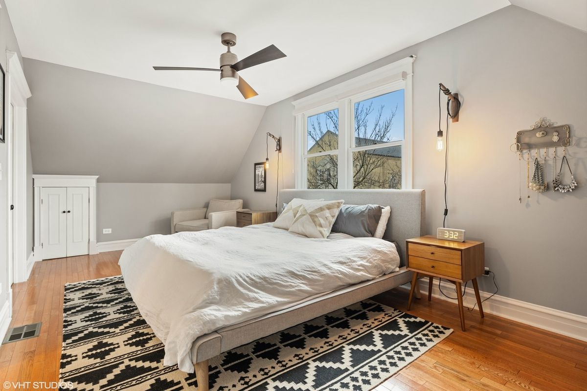 A bedroom with a bed against a window. It is sitting on blue and white rug. A nightstand is next to the bed.