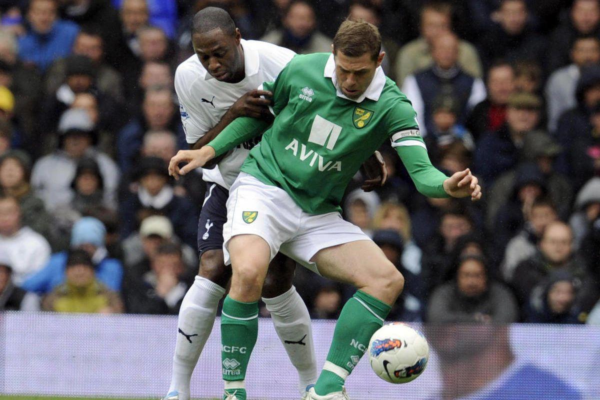 Tottenham Hotspur's Ledley King, left, tackles Norwich City's Grant Holt during their English Premier League soccer match at White Hart Lane stadium, London, Monday, April 9, 2012.