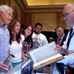 Reid Moon, right, shows a prayer book owned by Marie Antoinette at the Independence Through History Museum in the Grand America in Salt Lake City on Friday, July 5, 2013.