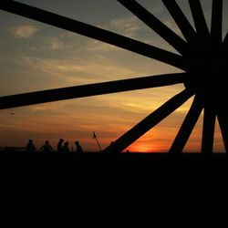 Sunset through a wagon wheel during a pioneer trek re-enactment in 2008.