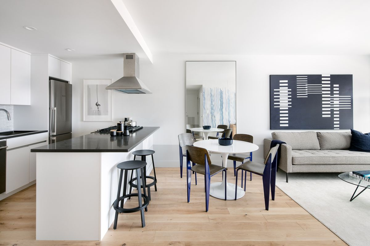 A dining area with hardwood floors, white walls, a round table, and a kitchen with cabinetry on the left side.
