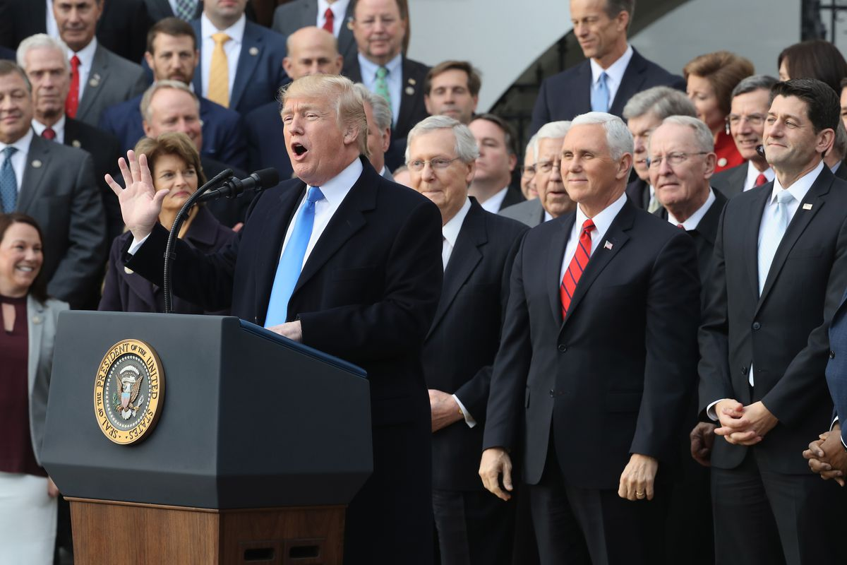 President Donald Trump and Republican lawmakers celebrate the passage of the Tax Cuts and Jobs Act in December 2017.