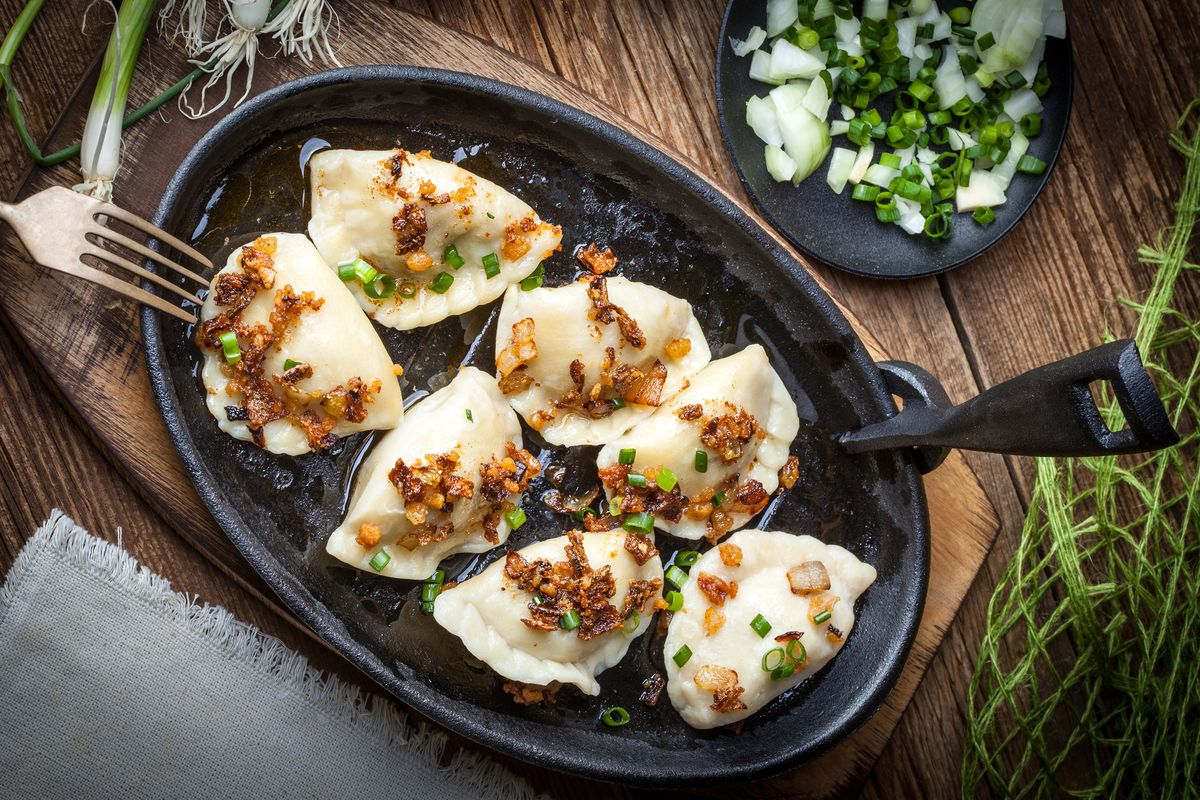 Dumplings with meat, onions and bacon on a cast iron skillet. Selective focus.