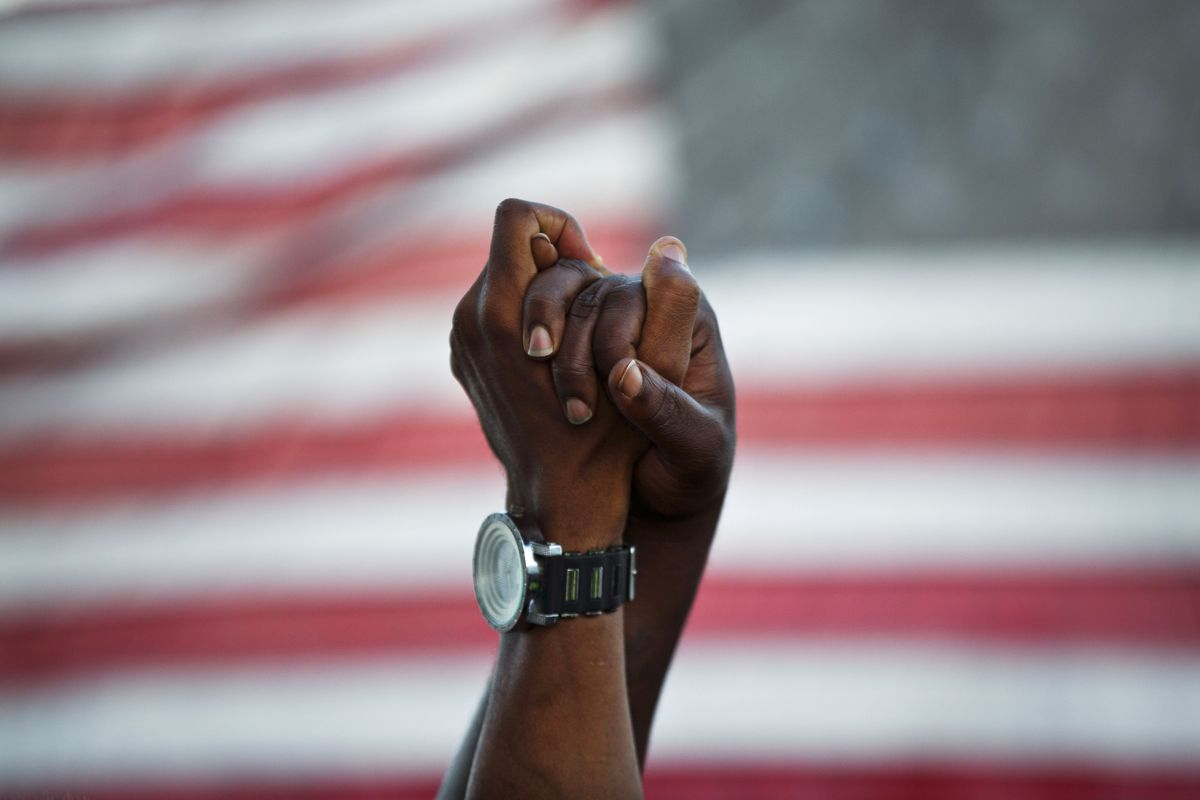 People join hands against the backdrop of an American flag.