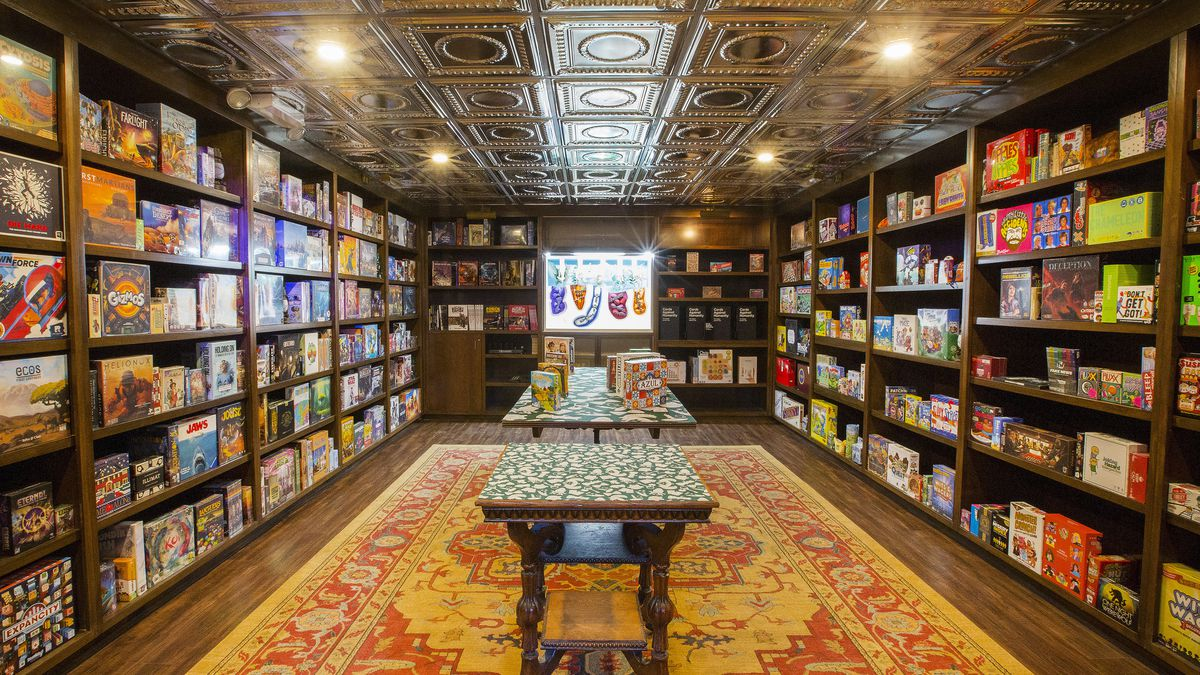 The game vault at Chicago Board Game Cafe is a richly appointed actual bank vault, with wooden walls lined with dark wooden shelves and filled with board games. In the center of the room, over a red and gold carpet, are long thin tables to take the games down and open them up.