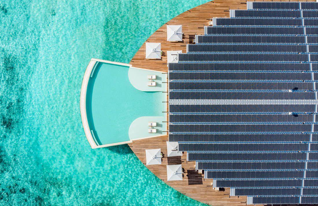 Aerial shot of resort with pool next to ocean