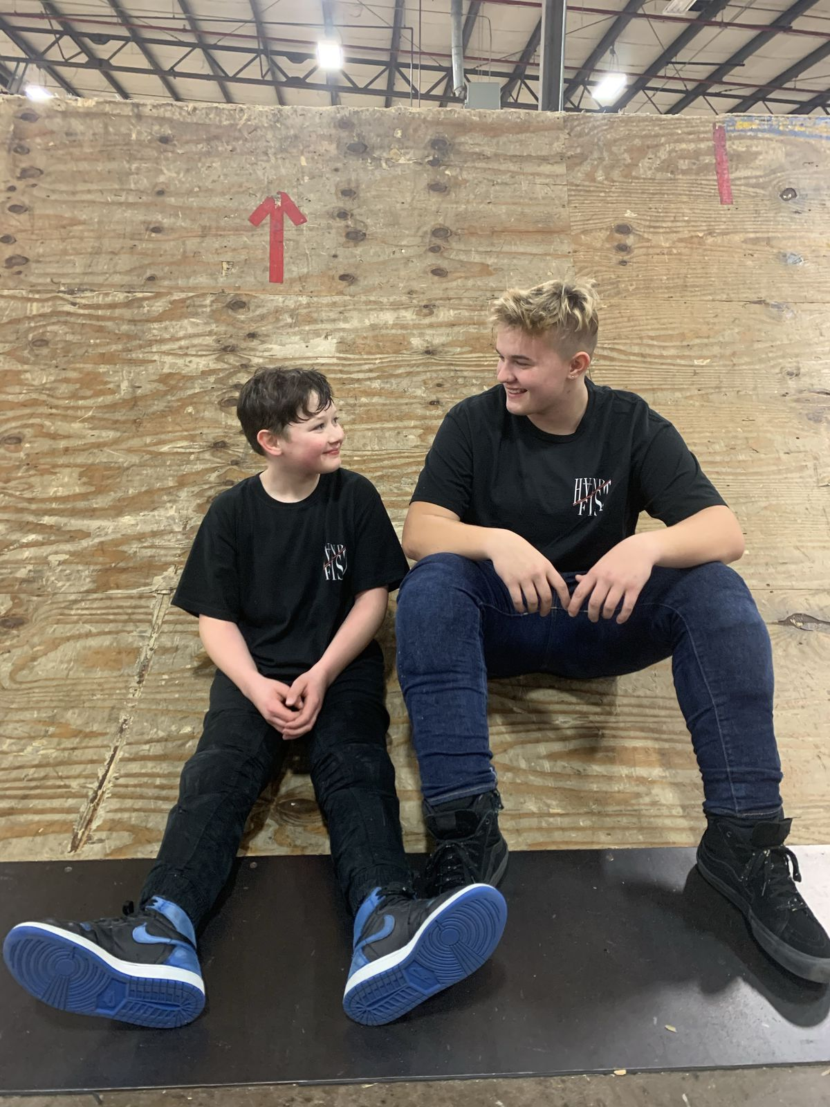 Hannah Roberts and a young boy looking at each other and smiling. They are willing black t-shirts and skateboarding shoes, and sitting on a wooden ramp inside a warehouse-type building.