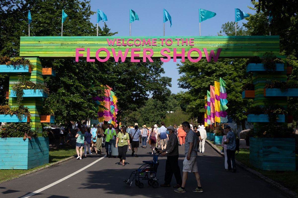The opening to the PHS Flower Show, held for the first time in history at FDR Park, with a sign that says welcome to the flower show