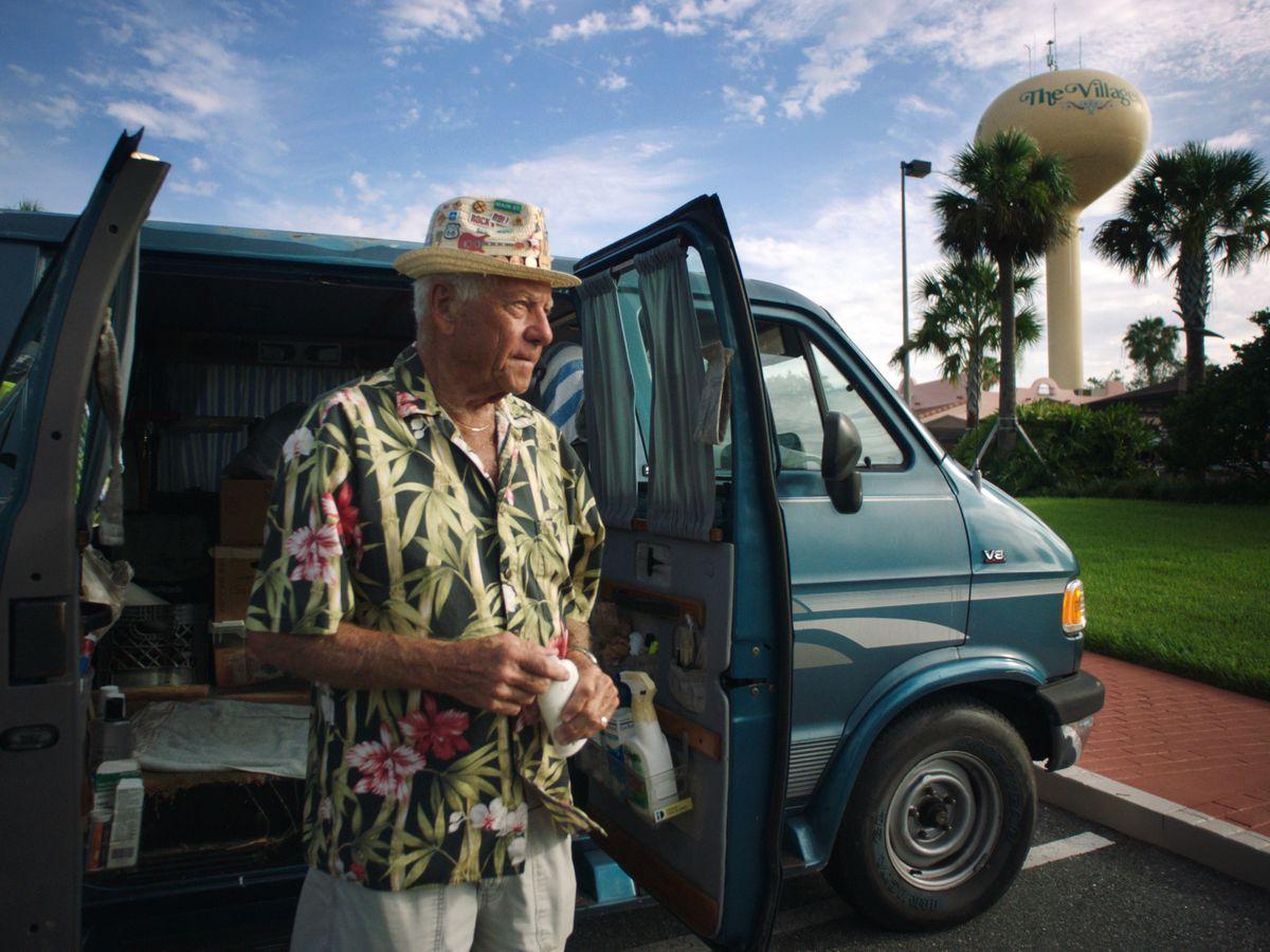 An elderly man wearing a Hawaiian shirt and a fishing cap stands outside a van.