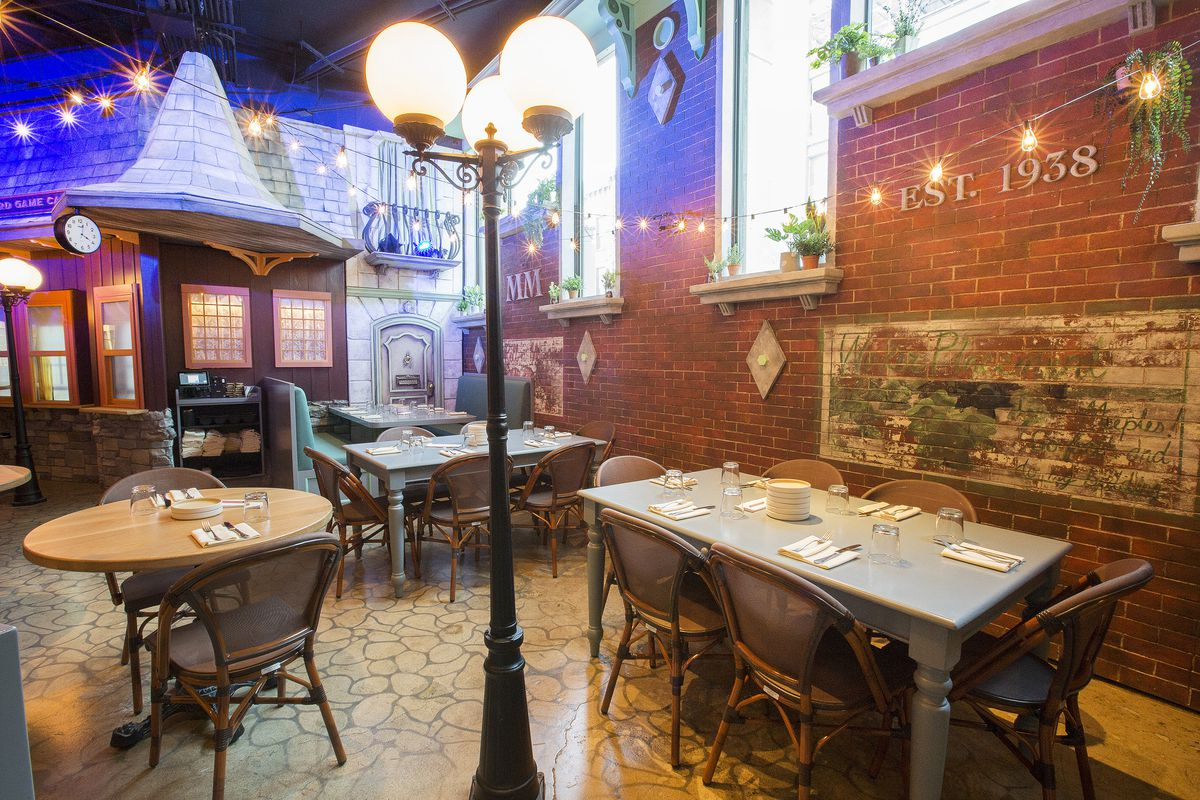 In the dining area, tables are a mix of round, homey rectangular kitchen tables, and diner-style booths. The walls and other elements are elegantly distressed, making it look lived in.