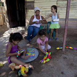 In this Nov. 4, 2013 photo, Evelina Gonzalez is with her daughter Evelin while her two nieces play nearby at her home in Maracay,Venezuela. Gonzalez is on a list of 31 breast cancer patients waiting to have tumors removed at one of the country's biggest medical facilities, Maracay's Central Hospital, before they spread and invade the women's lungs, brains or livers. She was supposed to have surgery in July following chemotherapy but was forced to shuttle from hospital to hospital in search of an available operating table, her tumor in the meanwhile more than doubling in size.